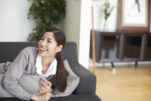 ソファーでクッションを抱いて笑う女性の写真素材 [FYI02966512]