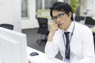 デスクで考えるビジネス男性の写真素材 [FYI02966514]