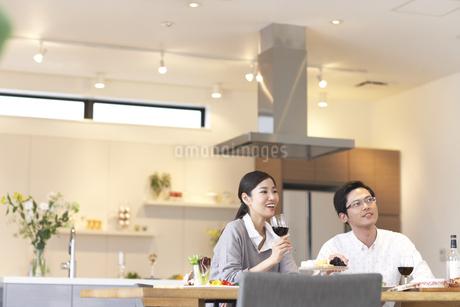 テーブルでワインを手に遠くを見る男女の写真素材 [FYI02966515]
