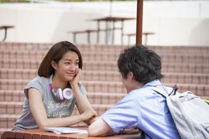 テーブルで目を合わせる男女の学生の写真素材 [FYI02966519]