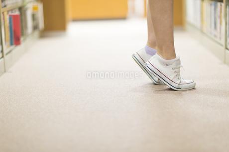 図書室で背伸びした女子学生の足元の写真素材 [FYI02966520]