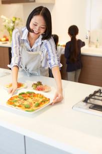 キッチンにピザを置く奥さんの写真素材 [FYI02966522]