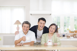 シニア夫婦の肩を抱いて笑う息子の写真素材 [FYI02966523]