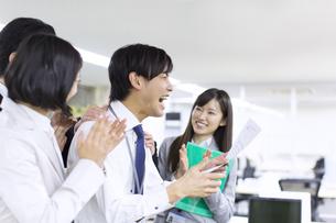 紙を手に喜ぶビジネス男性と拍手するスタッフの写真素材 [FYI02966524]