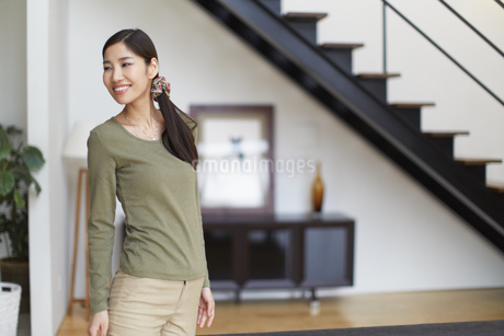リビングで振り向く女性のポートレートの写真素材 [FYI02966526]