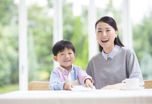 テーブルで笑顔の母と男の子の写真素材 [FYI02966534]
