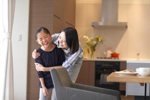 母に肩を抱かれながら笑う女の子の写真素材 [FYI02966545]