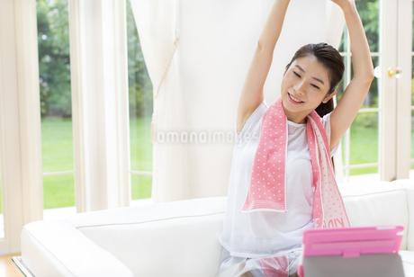 タブレットPCを見ながら伸びをする女性の写真素材 [FYI02966547]