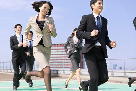 屋上で走るビジネス男女の写真素材 [FYI02966553]
