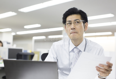 資料を手に考えるビジネス男性の写真素材 [FYI02966557]