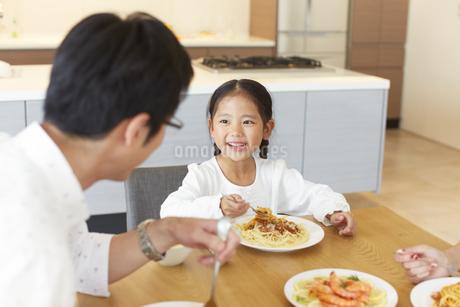 食事をしながら父に向いて笑う女の子の写真素材 [FYI02966564]