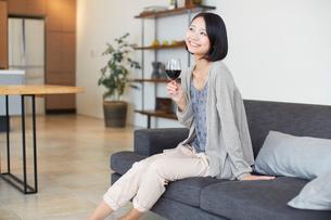 ソファーでワインを手に微笑む女性のポートレートの写真素材 [FYI02966565]