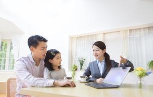 説明する訪問営業の女性と話を聞く父と娘の写真素材 [FYI02966569]