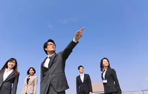 青空を背景に指をさす方向を見るビジネス男女の写真素材 [FYI02966576]