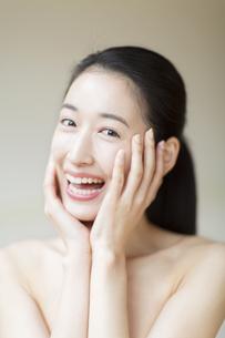頬に両手を添えた笑顔の女性の写真素材 [FYI02966578]
