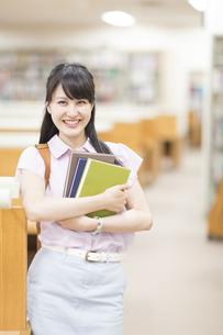 図書室で本を抱える女子学生のポートレートの写真素材 [FYI02966581]
