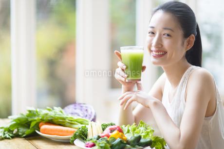 スムージーを手に微笑む女性の写真素材 [FYI02966585]