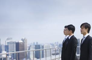 ビル群を見つめるように立つビジネス男性3人の写真素材 [FYI02966586]