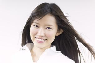 風を受けながら微笑む女性のアップの写真素材 [FYI02966589]