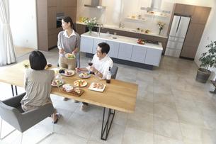 ホームパーティでワインや食事を手に外を見る男女の写真素材 [FYI02966594]