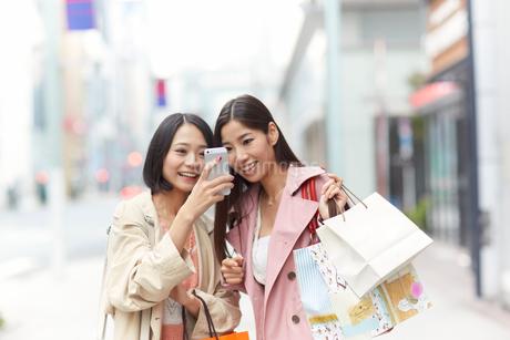買い物中にスマートホンを見て笑う女性二人の写真素材 [FYI02966598]