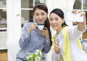 スマートフォンで写真を撮る2人の女性の写真素材 [FYI02966600]
