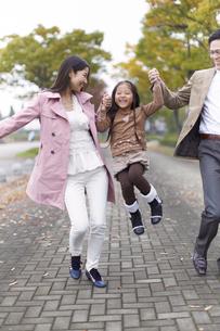 遊歩道で女の子を高く上げて笑い合う家族の写真素材 [FYI02966602]
