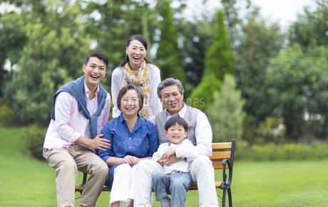 ベンチに揃って笑顔の三世代家族の写真素材 [FYI02966603]