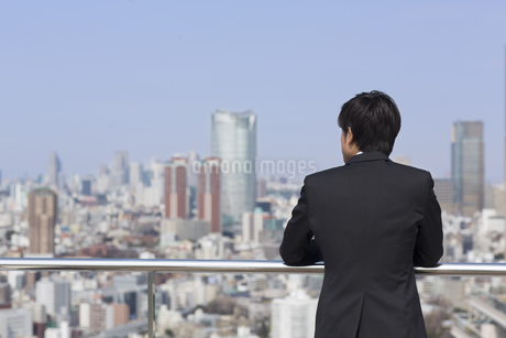 屋上でビル群を眺めるビジネス男性の後ろ姿の写真素材 [FYI02966611]