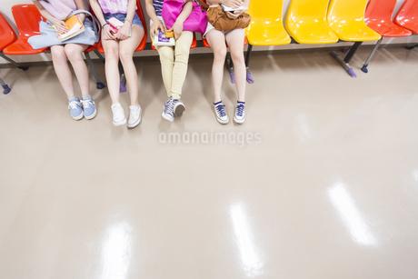 廊下の椅子に並んで座った女子学生の脚の写真素材 [FYI02966615]