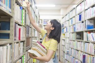 図書室で本を探す女子学生の写真素材 [FYI02966618]