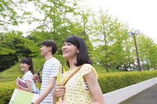 微笑みながら緑道を歩く学生たちの写真素材 [FYI02966620]