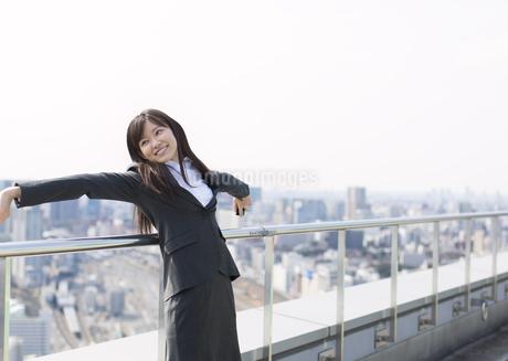屋上で横を見ながら伸びをするビジネス女性の写真素材 [FYI02966621]