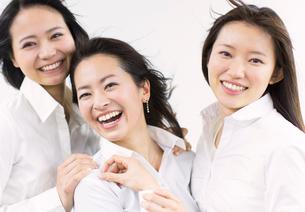 風を受けながら笑う女性3人の写真素材 [FYI02966624]