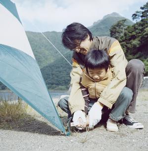 湖畔でテントを張る父と息子の写真素材 [FYI02966626]