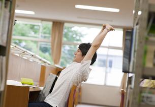 図書室で勉強中に伸びをする男子学生の写真素材 [FYI02966628]