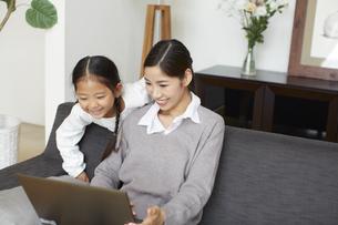 ソファーでノートパソコンを見る母と子の写真素材 [FYI02966629]