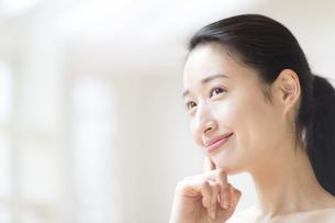 頬に指をあて微笑む女性の写真素材 [FYI02966631]