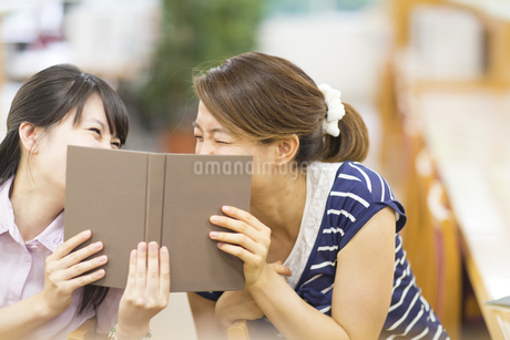 図書室で本で顔を隠して笑う2人の女子学生の写真素材 [FYI02966637]