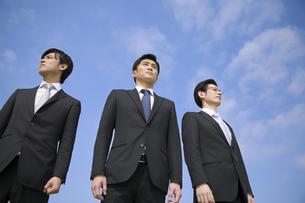 青空を背景に立つ3人のビジネス男性の写真素材 [FYI02966642]