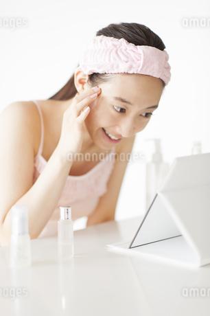 卓上ミラーでスキンケアをする微笑む女性の写真素材 [FYI02966643]