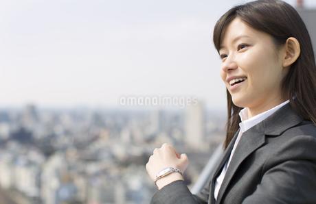 ビル群を背景に微笑むビジネス女性の写真素材 [FYI02966644]