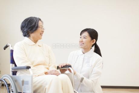 車椅子の患者に添う女性看護師の写真素材 [FYI02966646]