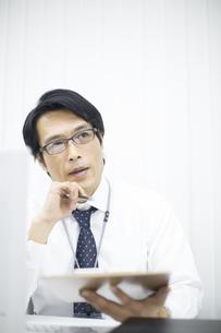 資料を見て考えるビジネス男性の写真素材 [FYI02966649]