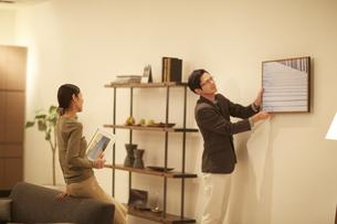 壁に写真を飾る男性とそれを見る女性の写真素材 [FYI02966651]