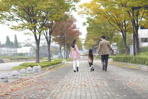 遊歩道を手をつないで歩く家族の写真素材 [FYI02966653]