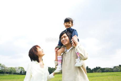 草原で娘を肩車する父と付き添う母の写真素材 [FYI02966655]