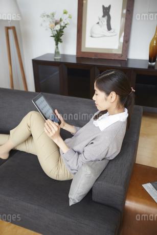 ソファーでスマートデバイスを見る女性の写真素材 [FYI02966656]