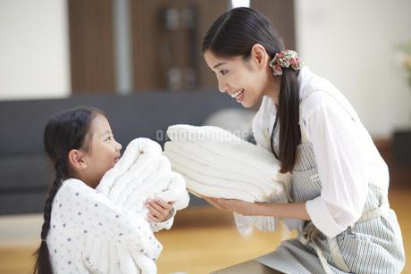 バスタオルを抱いて微笑み合う親子の写真素材 [FYI02966658]