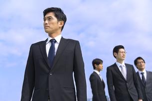 青空を背景に立つ4人のビジネス男性の写真素材 [FYI02966665]